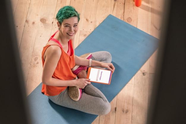 Im internet. fröhliche ansprechende grünhaarige sportlerin sucht bild im internet