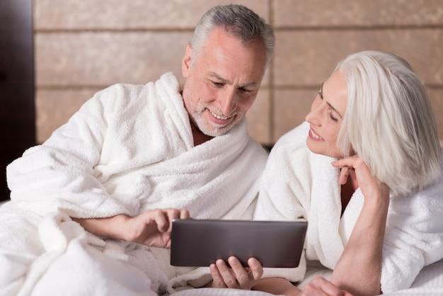 Im internet surfen. angenehmes lächelndes altes paar, das auf dem bett liegt und auf dem laptop im internet surft, während es freude ausdrückt