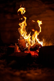 Im kalten winter brennt nachts im schnee ein lagerfeuer im schnee. die flamme des feuers erwärmt und leuchtet.