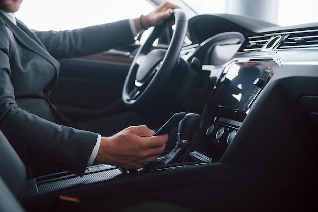 Im klassischen schwarzen anzug. moderner geschäftsmann, der sein neues auto im automobilsalon versucht.