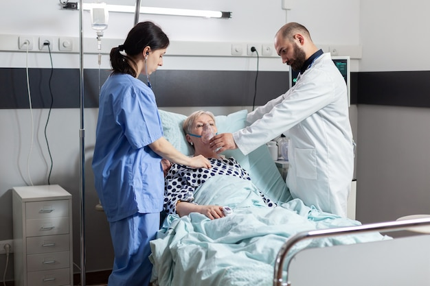 Im krankenhaus behandelte ältere frau ein- und ausatmen durch eine sauerstoffmaske, die im krankenhausbett liegt. medizinische krankenschwester, die das herz des patienten mit stethoskop hört