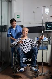 Im krankenhaus behandelter älterer mann, der im rollstuhl im krankenzimmer sitzt