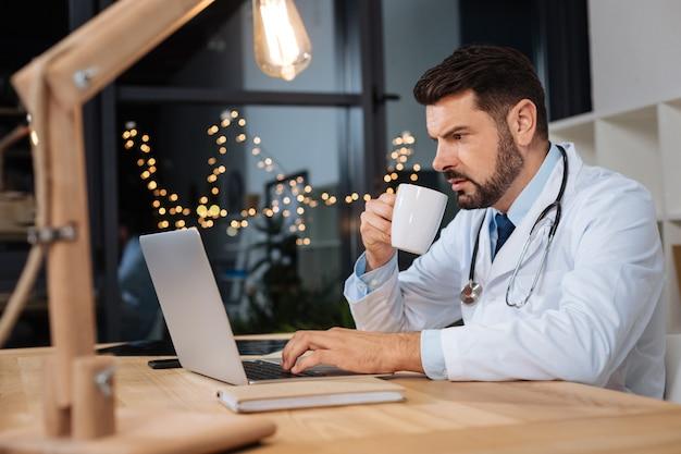 Im krankenhaus. ernsthafter, hart arbeitender männlicher arzt, der an einem laptop arbeitet und kaffee trinkt, während er eine nachtschicht im krankenhaus hat
