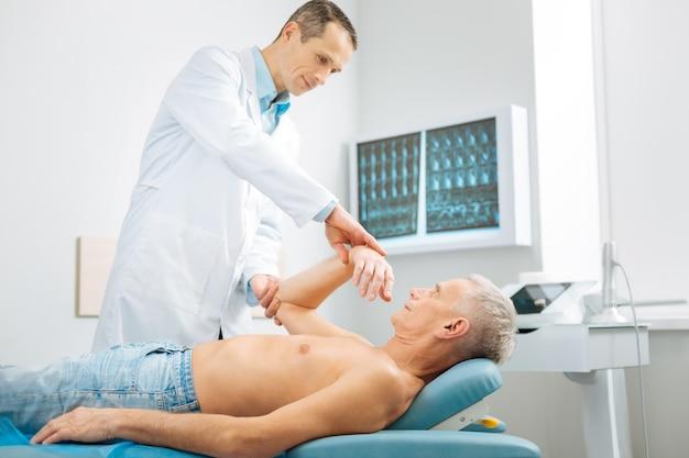 Im krankenhaus. netter ernsthafter männlicher arzt, der in der nähe seines patienten steht und eine medizinische untersuchung durchführt, während er im krankenhaus arbeitet