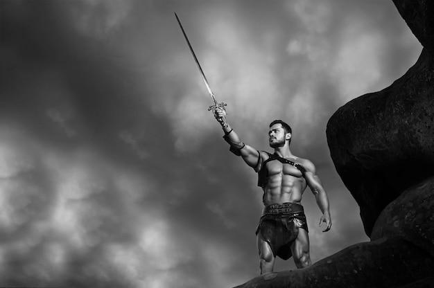 Im namen gottes. monochromes porträt eines mächtigen muskulösen gladiators, der sein schwert gegen den stürmischen himmel hält
