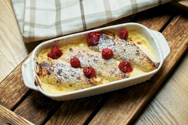 Im ofen gebackene französische crepes (pfannkuchen) mit hüttenkäse. in besonderer form gebackene pfannkuchen mit süßer sahne und beeren