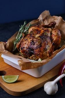 Im ofen gebackenes hähnchen mit gewürzen, zitrone, kräutern und jungen kartoffeln.