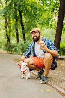 Im park spazieren gehen. moderner schöner mann, der sich ausgeruht fühlt, während er mit seinem kleinen weißen hund im park geht