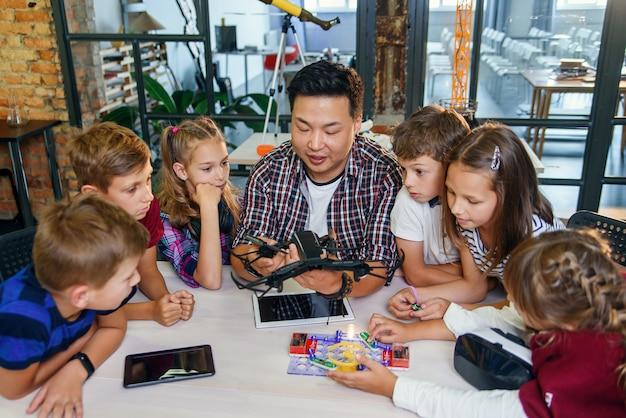 Im physik- und mechanikunterricht demonstriert der junge asiatische lehrer quadcopter für kaukasische schüler im unterricht in einer modernen smart school. wissenschaft, drohne, technik und zukunftskonzept.