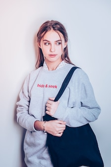 Im profil stehend. charmantes teenager-mädchen posiert in grauem langem hoodie mit schwarzer einkaufstasche