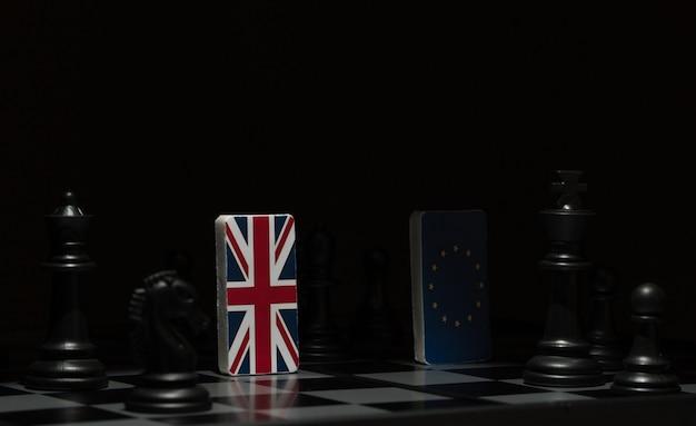 Im schatten hinterleuchtete figuren und flaggen der europäischen union und großbritanniens auf dem schachbrett