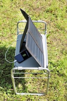 Im schatten verstecktes smartphone wird durch sonnenenergie aufgeladen