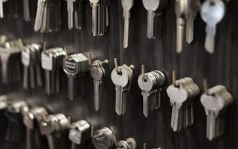 Im Schlosser hängen mehrere Schlüssel wie Haushalts- und Autoschlüssel zum Kopieren an der Wand