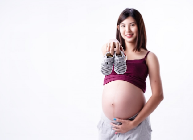 Im selektiven fokus der babyschuhe hielt von blured schwangere frau