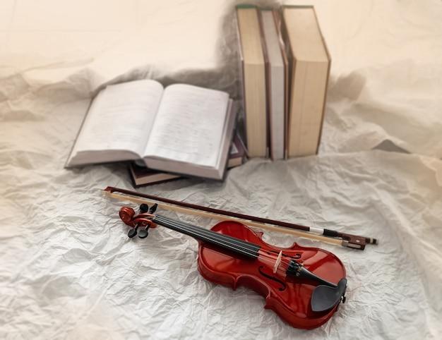 Im selektiven fokus der violine und des bogens setzte sich neben den gestapelten büchern