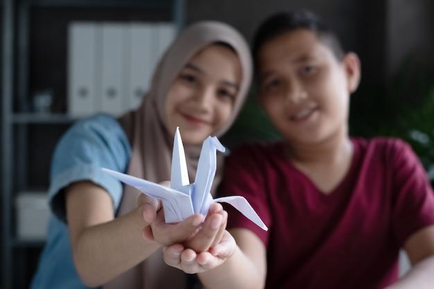 Im selektiven fokus des papierfaltvogels in den moslemischen studentenhänden