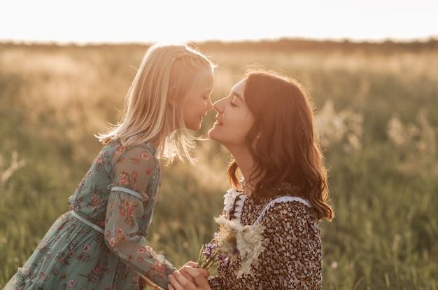 Im sommer spazieren ältere und jüngere schwestern gemeinsam in der natur. schwester umarmt und beruhigt