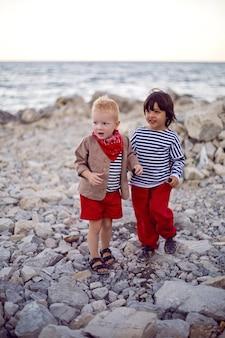Im sommer stehen zwei stilvolle jungen in westen an der kieselküste