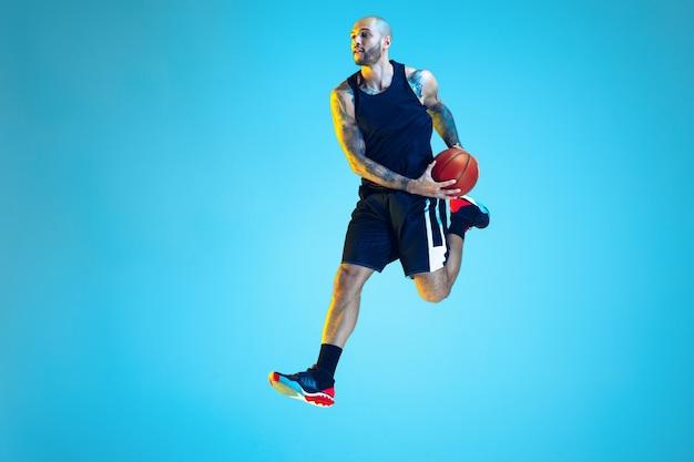 Im sprung. junger basketballspieler des teams, das sportbekleidungstraining trägt, in aktion übt, bewegung auf blauem hintergrund im neonlicht. konzept von sport, bewegung, energie und dynamischem, gesundem lebensstil.