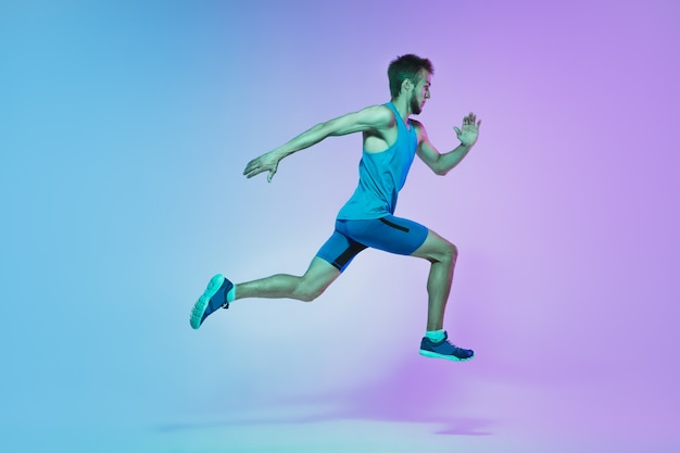 Im sprung portrait eines jungen kaukasischen mannes, der auf steigungsstudio joggt