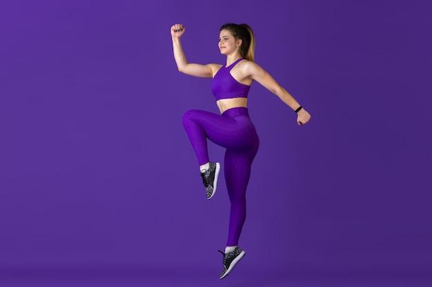 Im sprung. schöne junge sportlerin, die in einfarbigem purpurrotem porträt übt. sportliches kaukasisches fit-modelltraining. bodybuilding, gesunder lebensstil, schönheits- und aktionskonzept.
