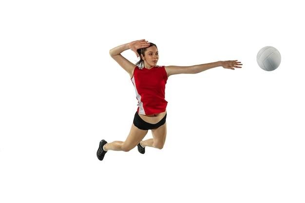 Im sprung und im flug. junge weibliche volleyballspielerin lokalisiert auf weißem studiohintergrund. frau in sportbekleidung und turnschuhtraining, spielend. konzept von sport, gesundem lebensstil, bewegung und bewegung.
