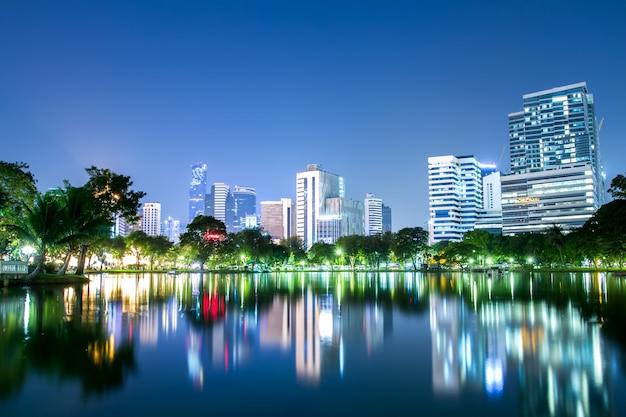 Im stadtzentrum gelegene landschaft lumpini-parks und bangkok-stadtzentrumsgeschäfts in der nacht