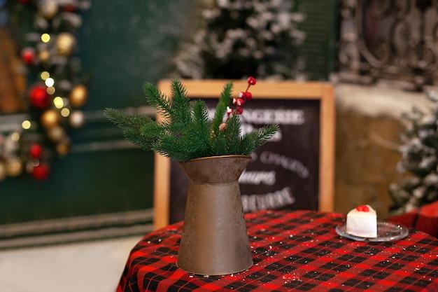 Im straßencafé stehen ein kupferkrug und tannenzweige auf dem tisch.