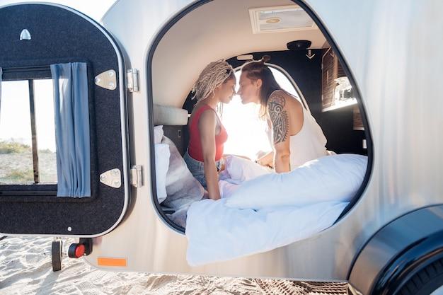 Im trailer. nettes liebespaar, das sich extrem glücklich und gut fühlt, wenn es zusammen in einem kompakten anhänger aufwacht