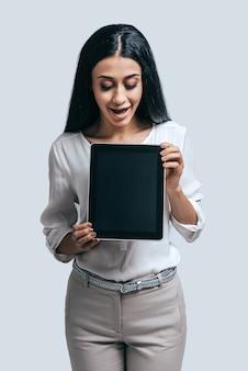 Im trend mit modernen technologien. attraktive junge frau, die digitales tablet mit überraschtem gesicht hält, während sie vor grauem hintergrund steht