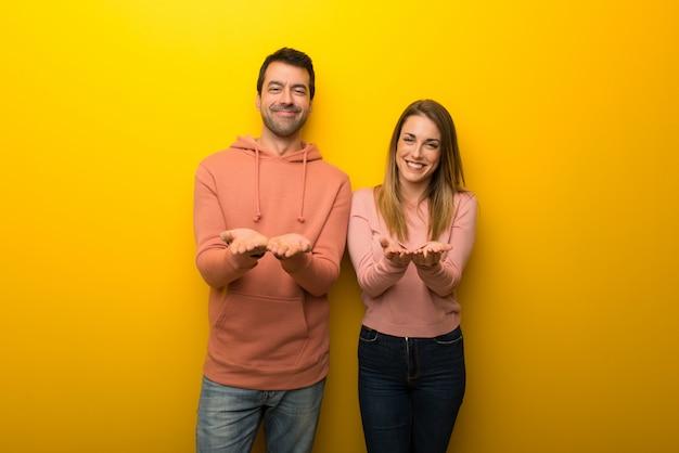 Im valentinstag gruppe von zwei leuten auf gelbem hintergrund, die copyspace auf der palme eingebildet hält, um eine anzeige einzufügen