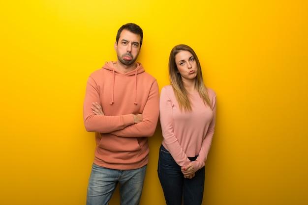 Im valentinstag gruppe von zwei leuten auf gelbem hintergrund mit traurigem und deprimiertem ausdruck