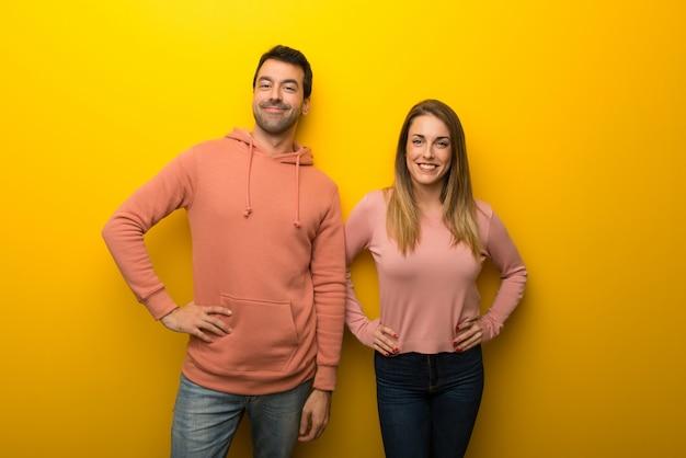 Im valentinstag gruppe von zwei leuten auf gelbem hintergrund posiert mit den armen an der hüfte und lacht, zur front schauen