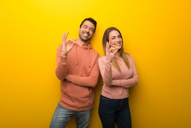 Im valentinstag gruppe von zwei leuten auf gelbem hintergrund zeigt ein ok zeichen mit den fingern