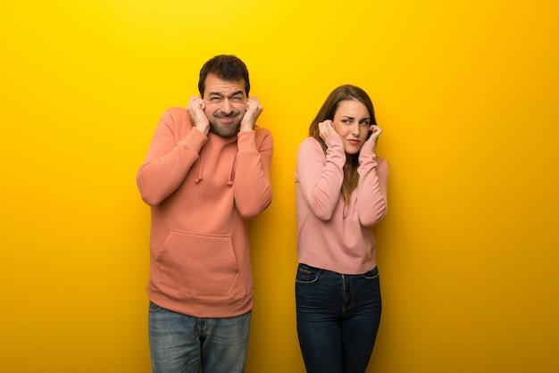 Im valentinstag gruppe von zwei leuten auf gelben hintergrundbedeckungsohren mit den händen. frustrierter ausdruck