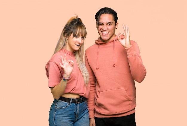 Im valentinstag junge paare, die ein okayzeichen mit den fingern über rosa hintergrund zeigen