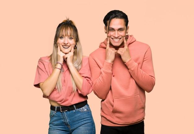 Im valentinstag junge paare, die mit einem glücklichen und angenehmen ausdruck über rosa hintergrund lächeln