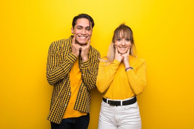 Im valentinstag junge paare über vibrierendem gelbem hintergrund, der mit einem glücklichen und angenehmen ausdruck lächelt