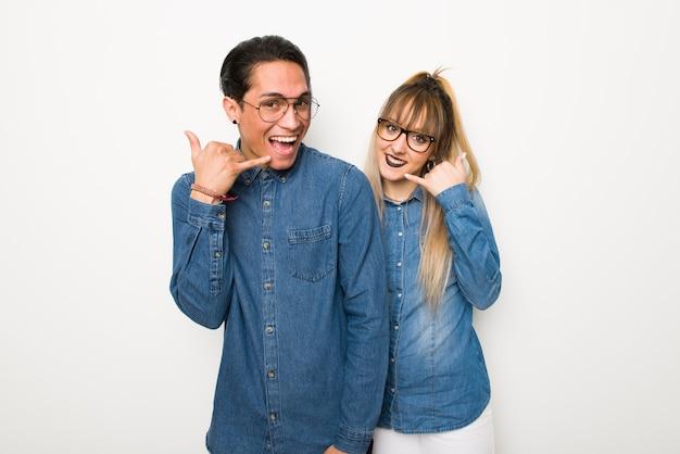 Im valentinstag junges paar mit brille telefon geste machen. ruf mich zurück zeichen