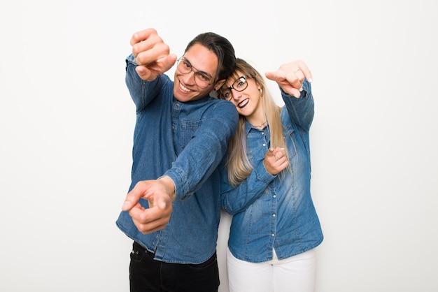Im valentinstag junges paar mit brille zeigt finger auf sie beim lächeln
