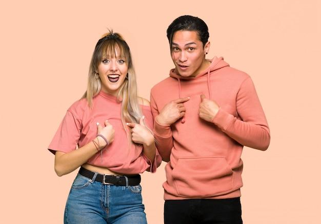 Im valentinstag junges paar mit überraschung gesichtsausdruck über rosa hintergrund