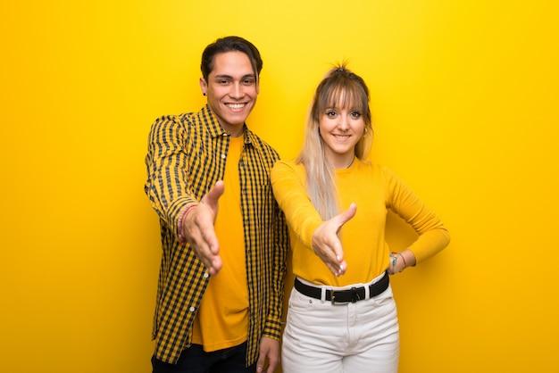 Im valentinstag junges paar über lebendigen gelben hintergrund händeschütteln für ein gutes geschäft