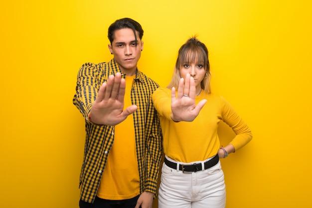 Im valentinstag junges paar über lebendigen gelben hintergrund machen stop geste eine situation zu verweigern, die falsch denkt