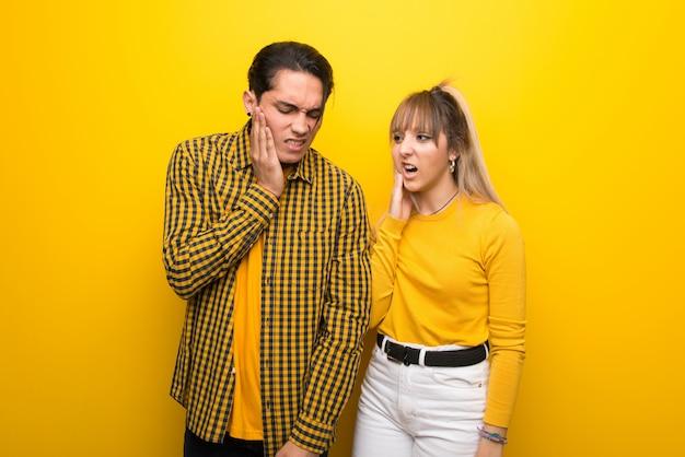 Im valentinstag junges paar über lebendigen gelben hintergrund mit zahnschmerzen