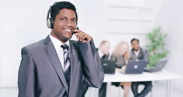 Im vordergrund das mitarbeiter-callcenter mit headset an der wand des büros
