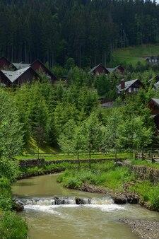 Im vordergrund fließt ein fluss mit schlammigem wasser und einem kleinen wasserfall. dahinter sieht man die hotelhäuser in der nähe des berges hinter grünen bäumen