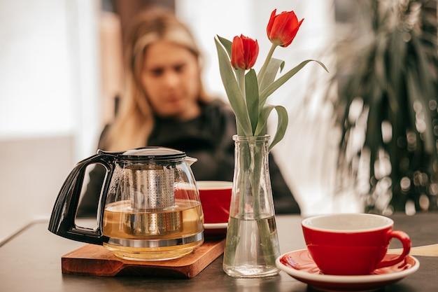 Im vordergrund tassen und glasteekanne mit tee, im hintergrund porträt einer unscharfen frau