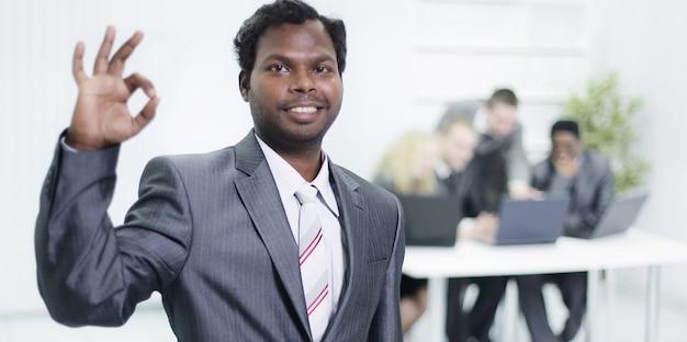 Im vordergrund zeigt ein junger geschäftsmann die geste ok und steht im büro