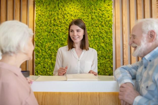 Im wellnesscenter. hübsche kosmetikerin im gespräch mit einem reifen paar an der rezeption eines wellnesscenters
