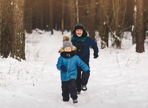 Im winter rennen zwei jungen im park. im freien spielen